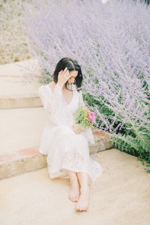 Photo of Woman Sitting While Holding Bouquet of Flowers