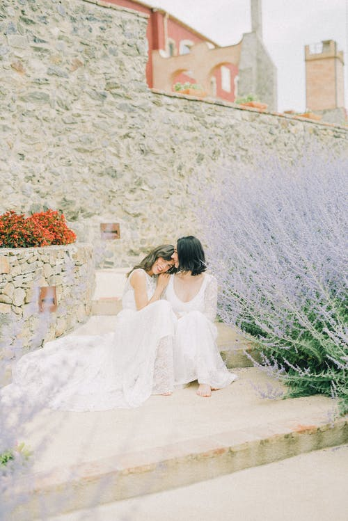 Foto Von Frauen Im Weißen Hochzeitskleid, Das Auf Betonboden Sitzt