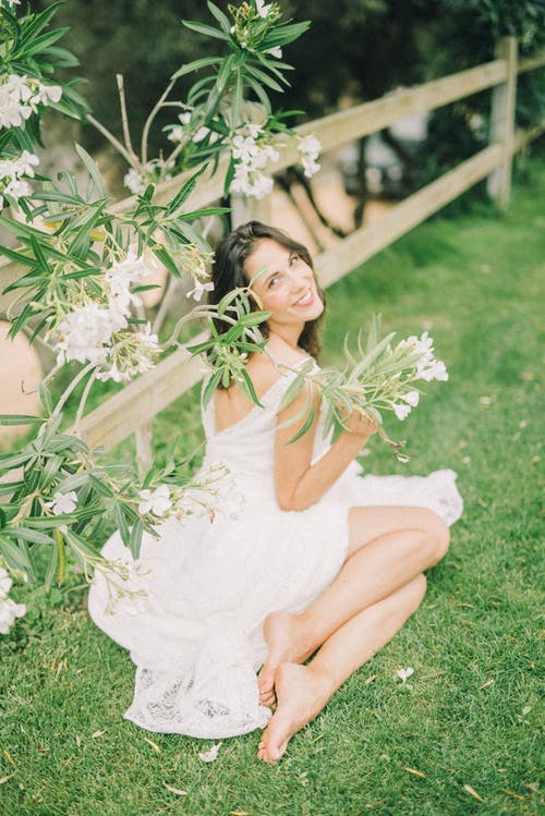 Woman in Wedding Dress Sitting on Grass While Smiling