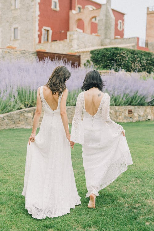 Photo of Two Women in White Wedding Dress Walking on Grass Field
