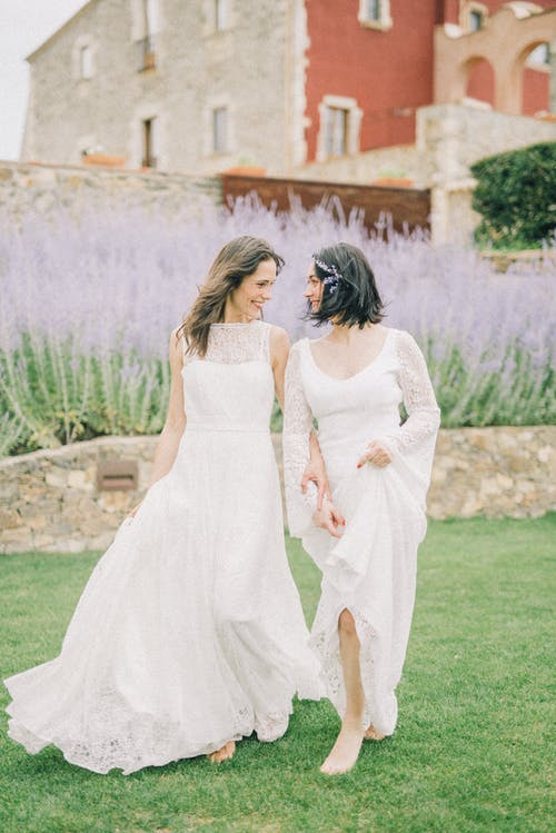 Photo of Two Women Looking at Each Other While Walking on Grass Field