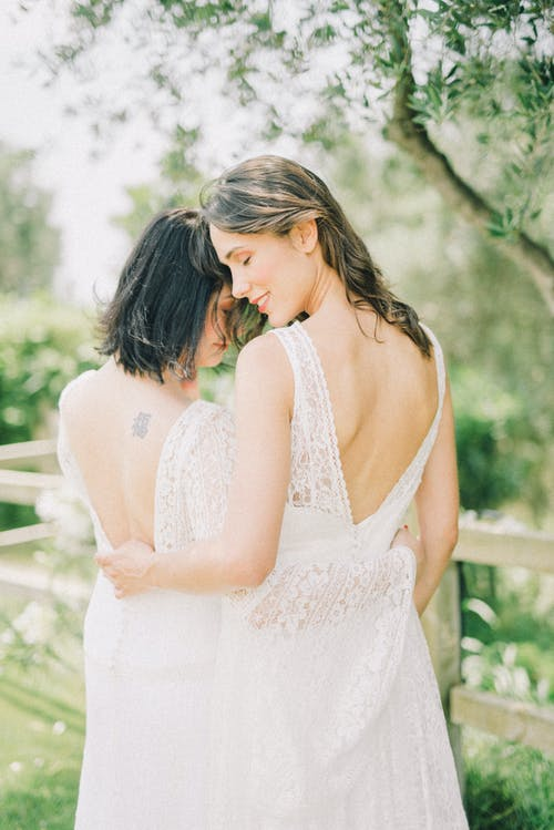 Photo of Women in White Wedding Dress Hugging Each Other