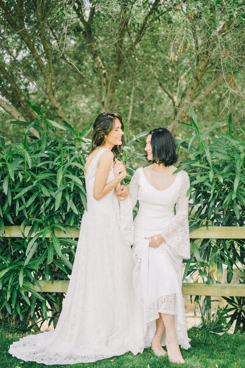 Photo of Women in White Wedding Dress Looking at Each Other