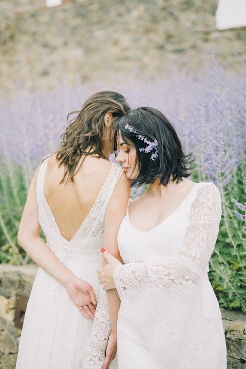 Фотография женщин в белом свадебном платье, стоящих рядом друг с другом
