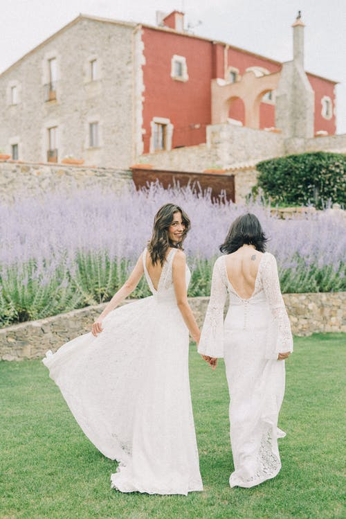 Photo of Women in White Wedding Dress Walking on Grass