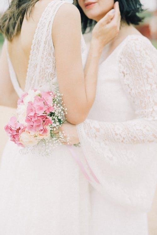 Photo of Women in White Lace Dress While Holding Bouquet of Flowers