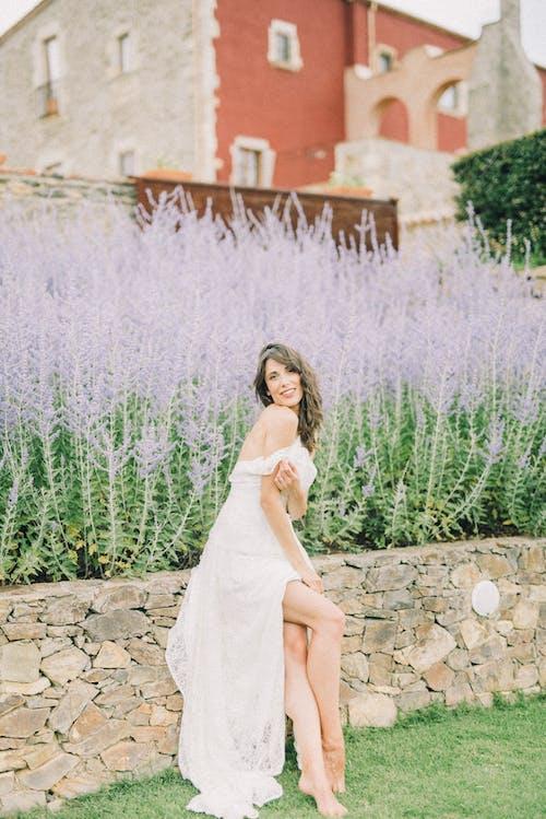Woman in White Wedding Dress Sitting Near Purple Flowers