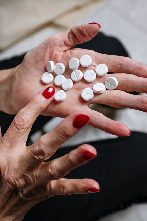 White and Orange Medication Pill on Persons Hand