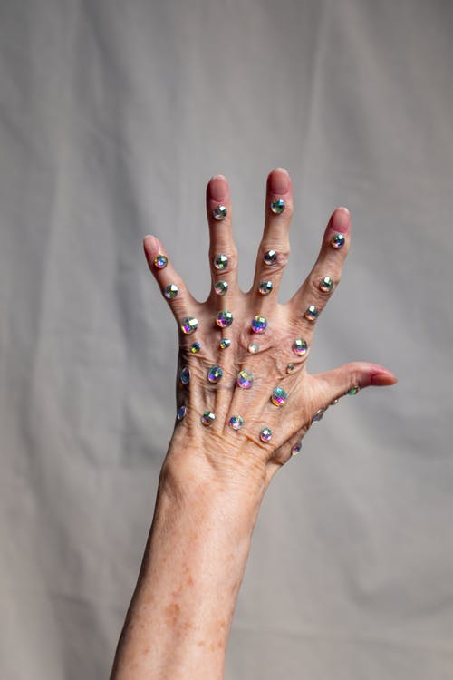 Person With Blue Glitter on Left Hand