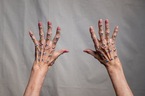 Person With Blue Manicure on White Textile