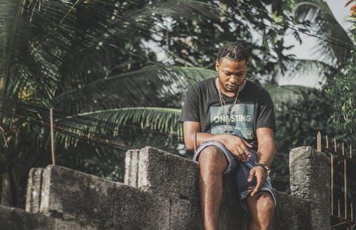 Man in Black Crew Neck T-shirt Sitting on Concrete Blocks
