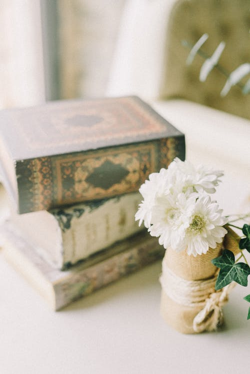 White Flowers Near Stack of Books