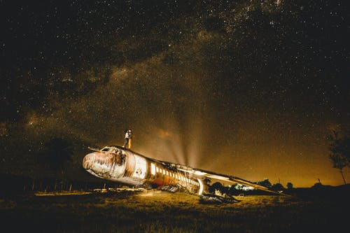 Anonymous couple of travelers embracing on abandoned plane at dusk