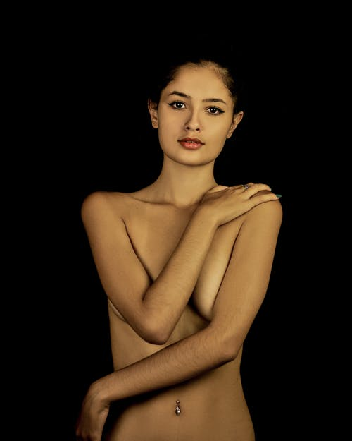 Undressed young woman covering bare boobs