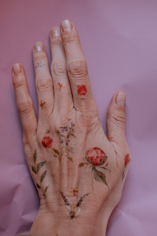 Photo of Flower Tattoos on Person's Left Hand