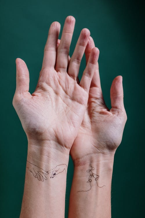 Photo of Person's Hand With Tattoo on Wrist