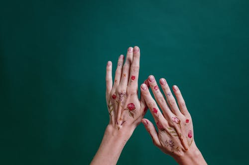 Person's Hands With Flower Tattoos Against Green Background