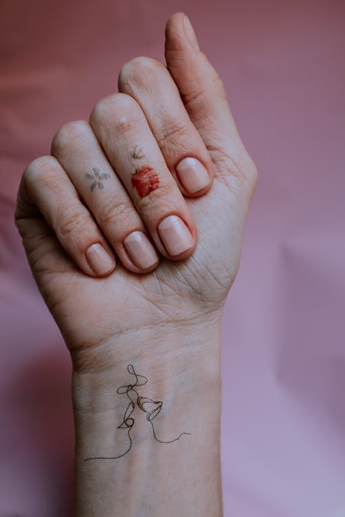 Photo of Person's Hand With Manicured Nails and Tattoos