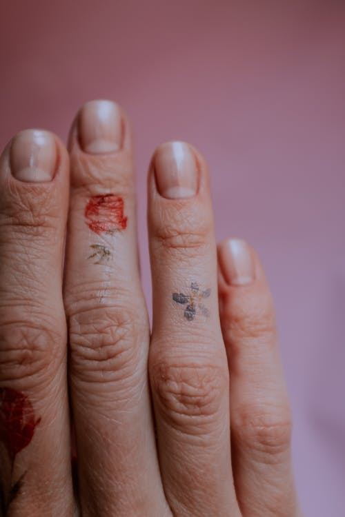 Close-Up Photo of Person's Fingers Against Pink Background