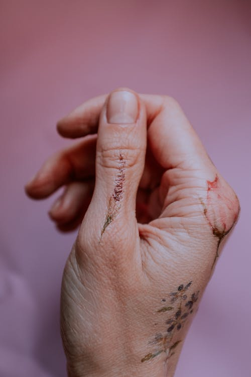 Person's Right Hand With Flower Tattoos