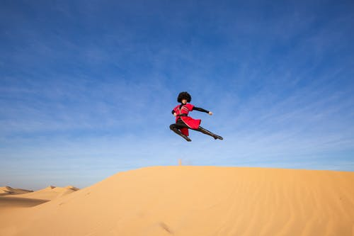 Photo of Person Dancing on Desert Under Blue Sky