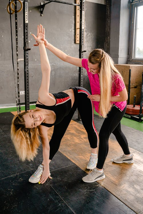 Photo of Woman Helping Another Woman in Exercising