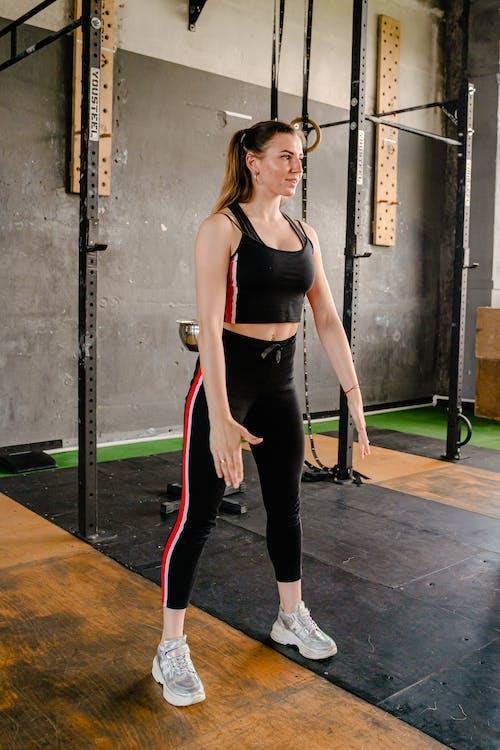 Woman in Black Tank Top and Black Pants Standing on Brown Wooden Floor