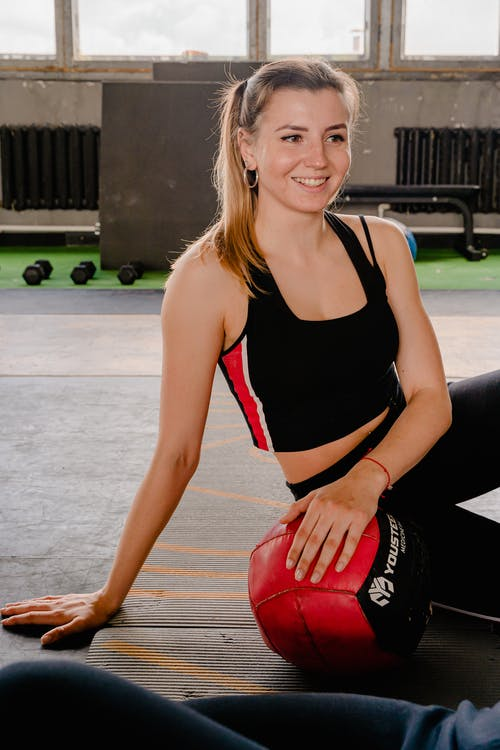 Photo of Woman Smiling While Sitting on Yoga Mat