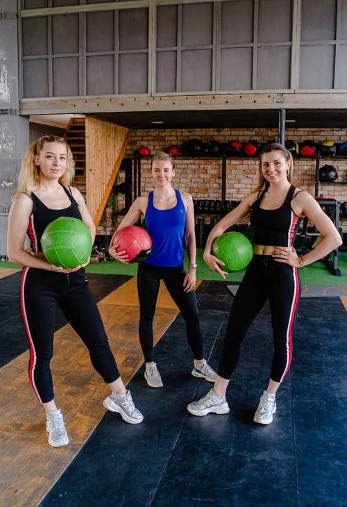 Photo of Three Women Standing While Holding an Exercise Ball