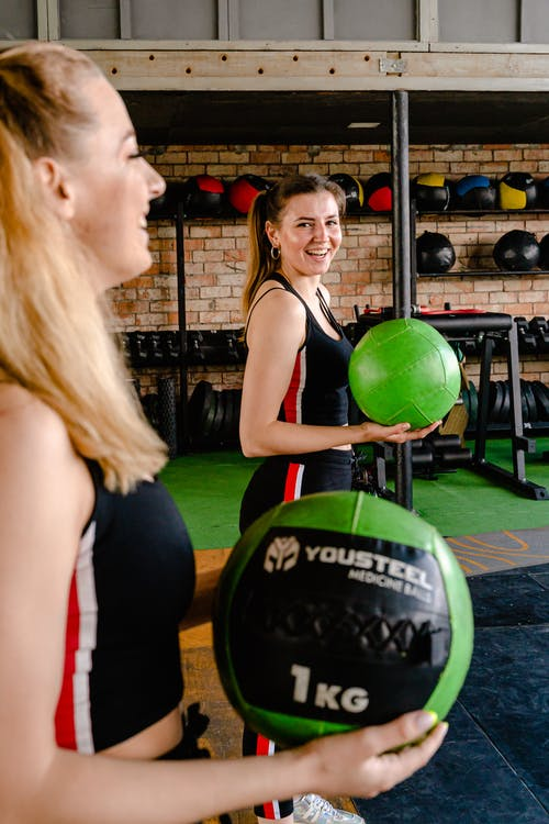 Photo of Woman Smiling While Holding Green Exercise Ball