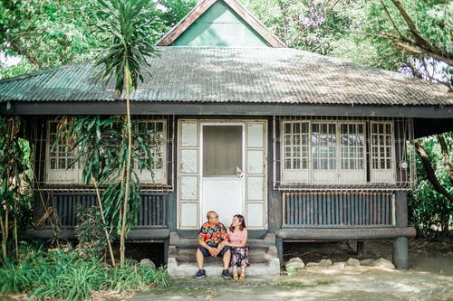 Photo of Couple Sitting in Front of House