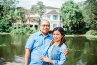 Photo of Couple Wearing Blue Button Up Shirt While Smiling
