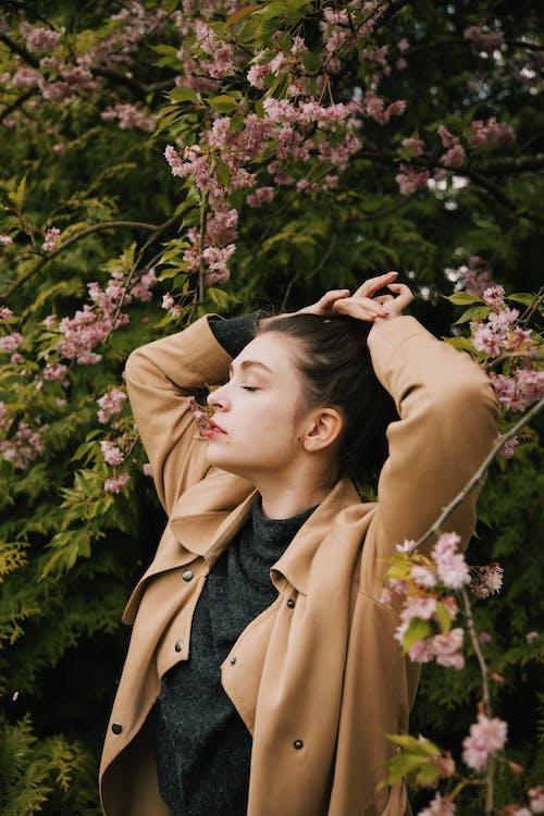 Woman in Brown Coat Standing Near Pink Flowers