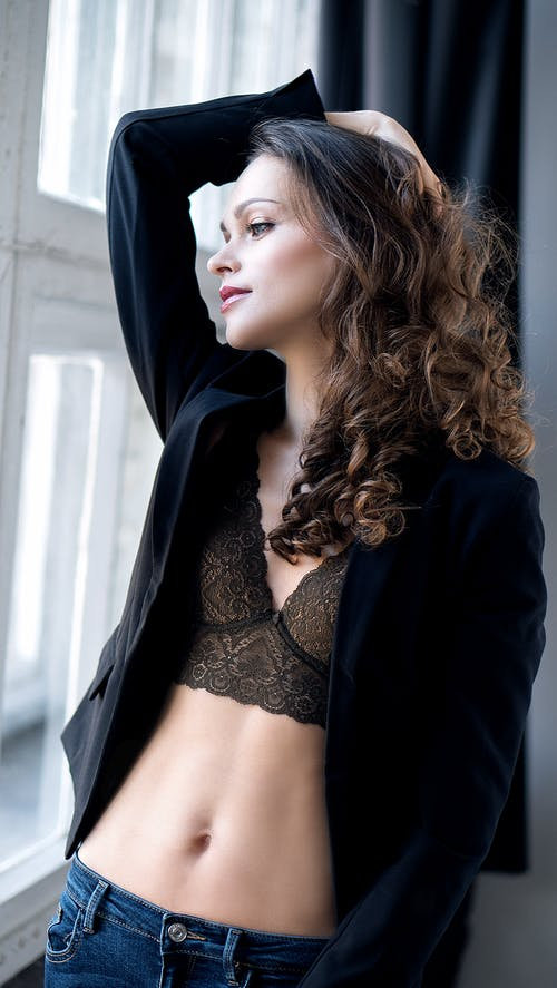 Alluring slim woman in bra touching hair near window