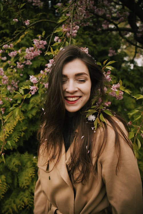 Photo of Woman in Brown Coat Smiling While Standing Near Pink Flowers