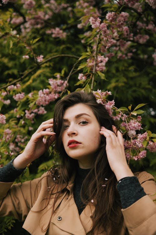 Photo of Woman in Brown Coat Standing Near Pink Flowers