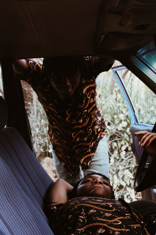 Content African American men in casual clothes resting in car with opened door