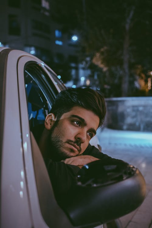 Photo of Man Leaning on Car Window