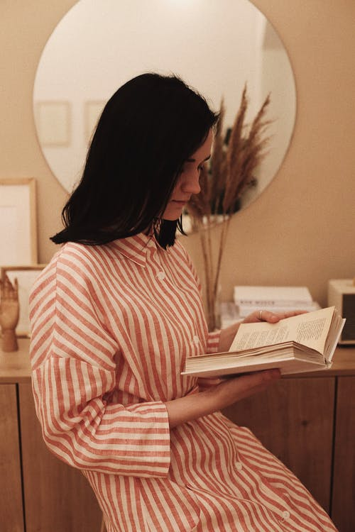 Woman in White and Red Striped Long Sleeve Shirt Reading Book