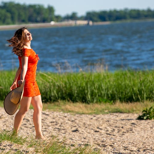 Woman in Orange Dress Walking on Sand
