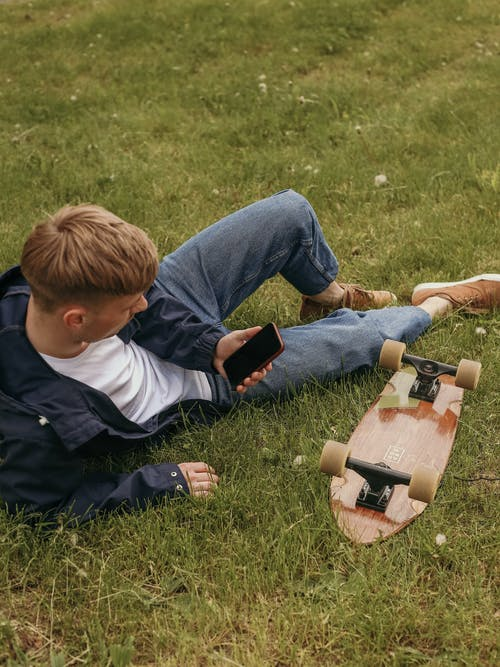 Boy in Blue and White Long Sleeve Shirt Playing Brown Acoustic Guitar on Green Grass Field