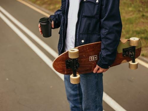 Person in Blue Denim Jacket Holding A Skateboard