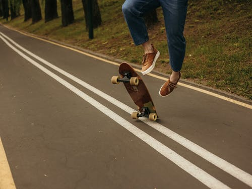 Person in Blue Denim Jeans and Brown Leather Boots Sitting on Brown Skateboard on Road during