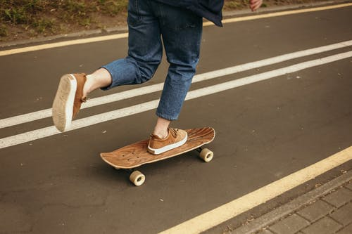 Person in Blue Denim Jeans and Brown Shoes Standing On A Skateboard on Gray Concrete Road