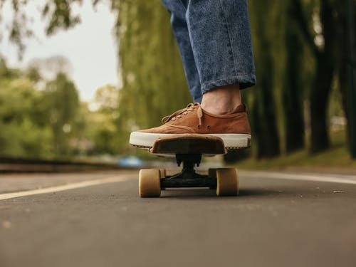 Person in Blue Denim Jeans and Brown Leather Shoes Riding on Skateboard