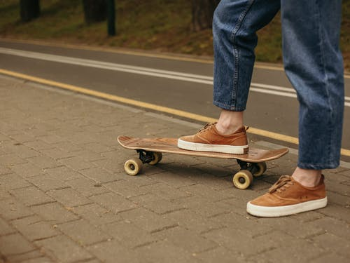 Person in Blue Denim Jeans and Brown Leather Shoes Riding Skateboard