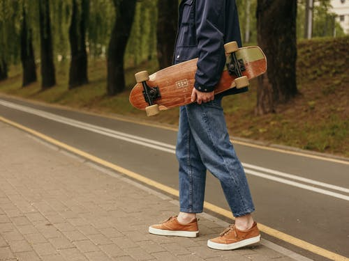 Man in Blue Denim Jeans and Black Jacket Holding A Skateboard