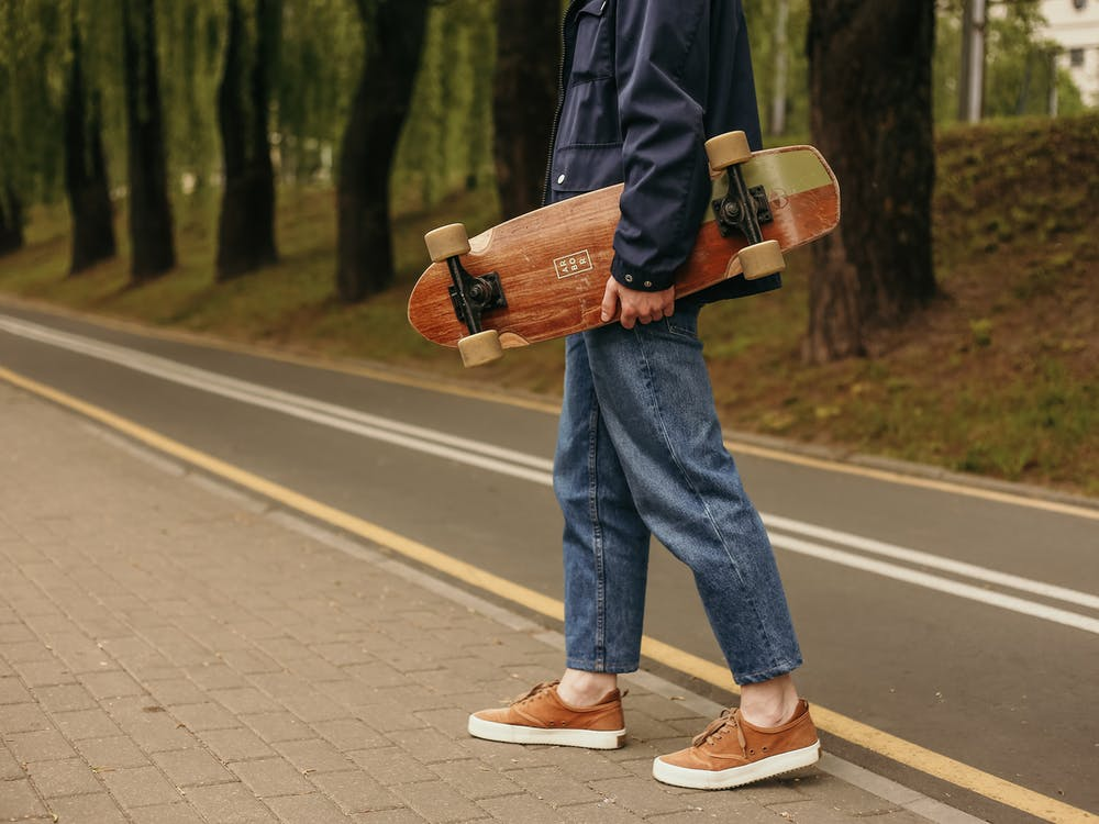 Man in Blue Denim Jeans and Black Jacket Holding A Skateboard