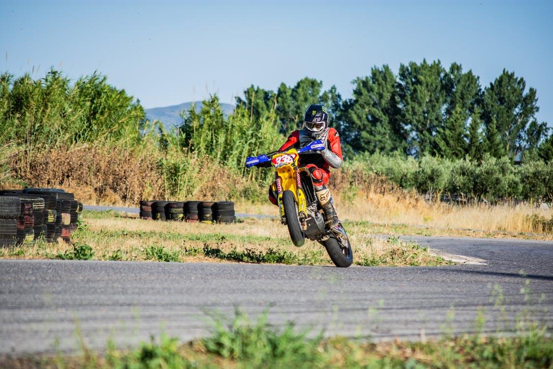 Man in Orange and Black Jacket Riding Motocross Dirt Bike