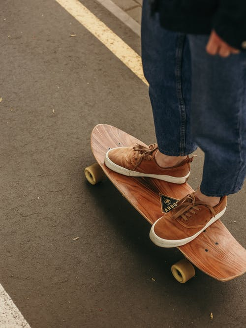 Person in Blue Denim Jeans and Brown Shoes Riding Longboard